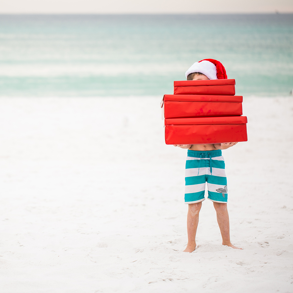 Little boy holding presents at the beach