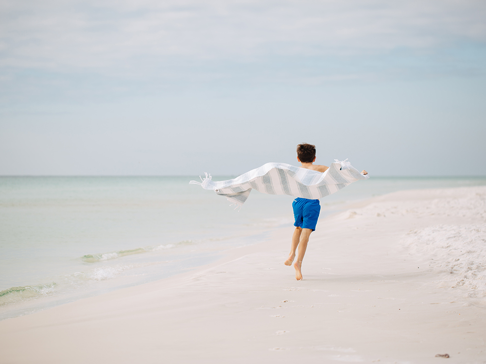 Young boy running down the beach with a beach blanket